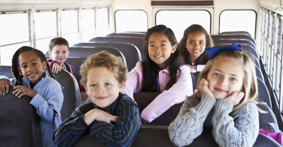 Multi-ethnic school children (ages 5 to 9) inside school bus. Focus on Asian girl (8 years).